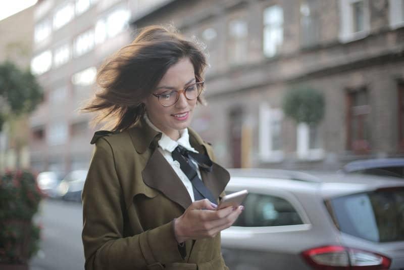 Eine zufriedene Frau in einem grünen Mantel liest eine Nachricht auf ihrem Handy