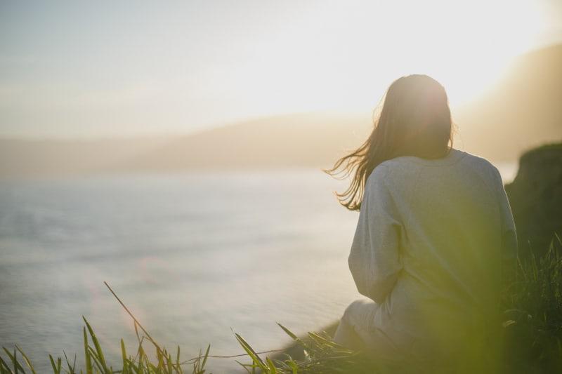 Frau, die graues langärmeliges Hemd mit Blick auf das Meer trägt