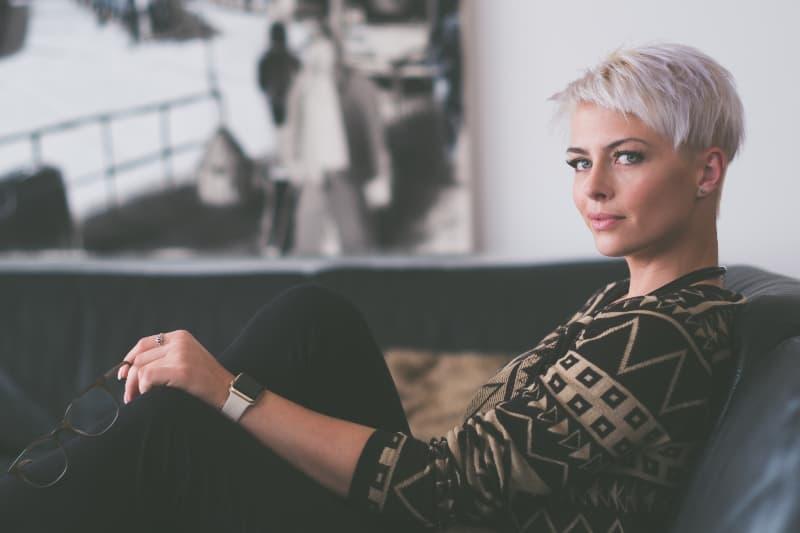 Frau sitzt auf Sofa hält Brille(1)
