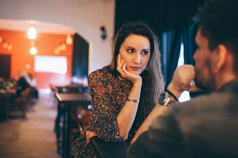 Frau stützte sich auf ihre Hand und sah Mann im Café an