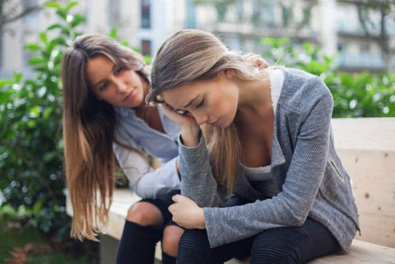 Frau tröstet ihren Freund an der Parkbank