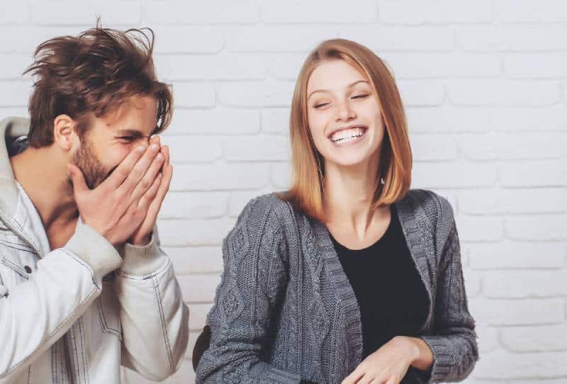 Glückliches junges Paar lachen auf weißem Backsteinhintergrund