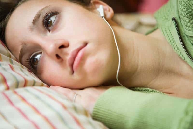 Nahaufnahmefoto der Frau, die traurige Musik mit Kopfhörern hört