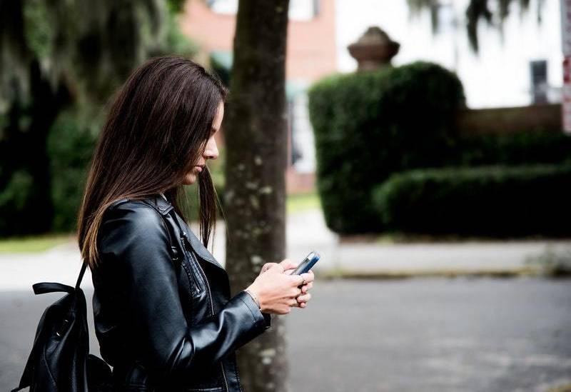 Seitenansicht der Frau, die draußen auf ihrem Telefon tippt