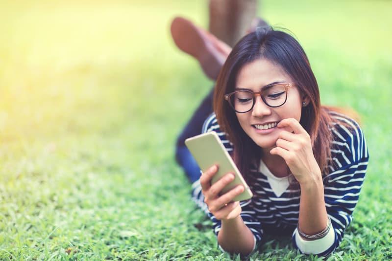 asiatische Frau hält Telefon