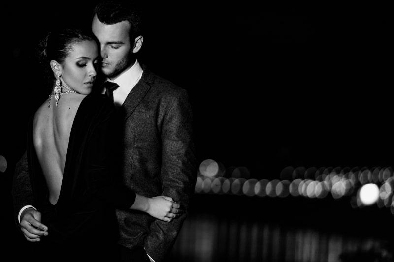 ein Mädchen in einem eleganten Kleid in den Armen ihres Mannes