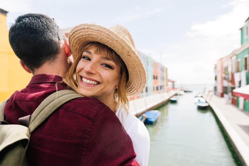 eine lächelnde Frau in den Armen eines Mannes in Venedig