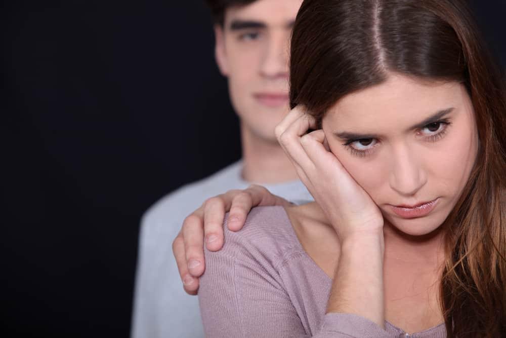 eine unglückliche Frau gegenüber dem Mann, der ihre Schulter hält