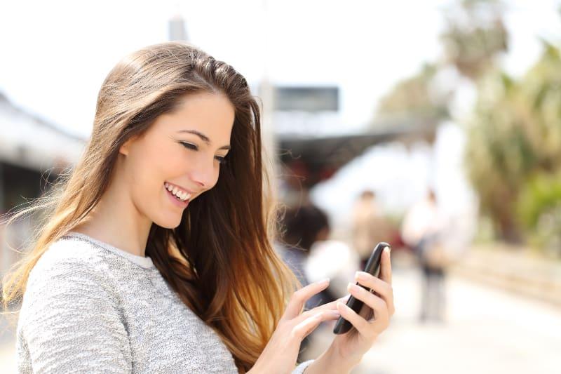 glückliches Mädchen SMS auf Smartphone