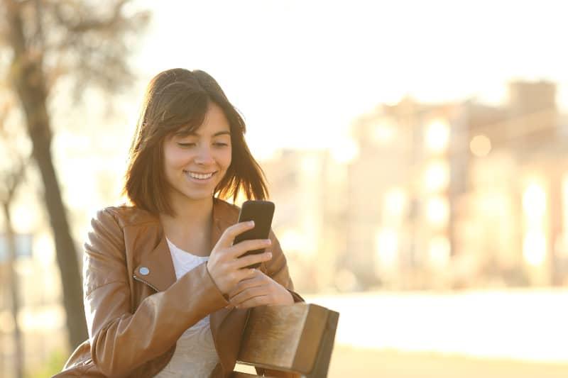 glückliches Mädchen, das in einem Stadtpark sitzt