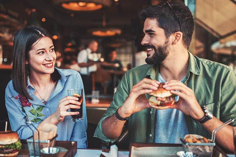 lächelndes junges Paar, das sich im Restaurant schaut