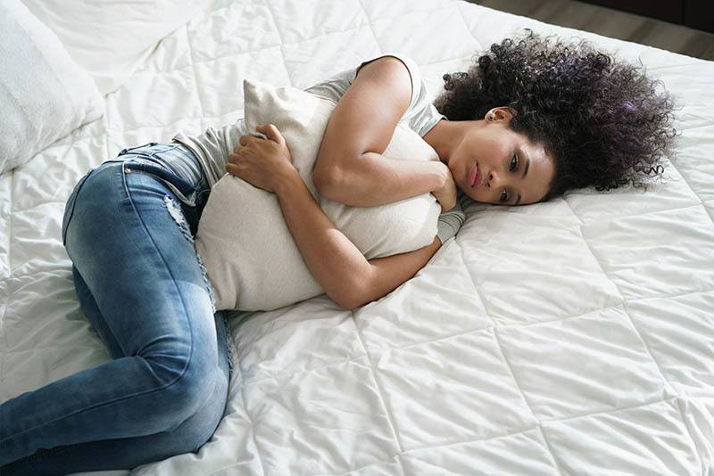 nachdenkliche Frau, die Kissen auf Bett umarmt