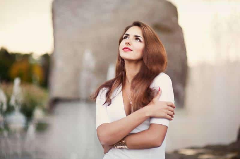 schöne Frau umarmt sich in der Nähe des Brunnens