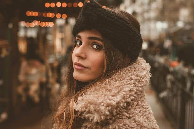 schöne junge Brünette mit Hut und brauner Jacke draußen