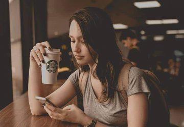 Frau, die auf ihrem Telefon tippt, während sie Starbucks-Kaffee trinkt
