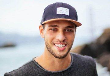 ein Mann mit einer Mütze und schönen weißen Zähnen