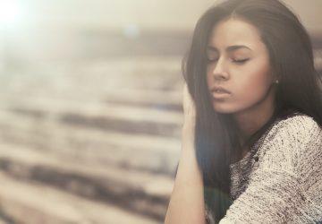 Draußen sitzt mit geschlossenen Augen eine schöne Brünette in einem grauen Pullover