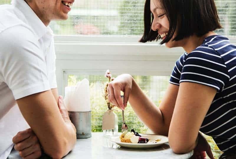 lächelndes Paar, das am Tisch spricht