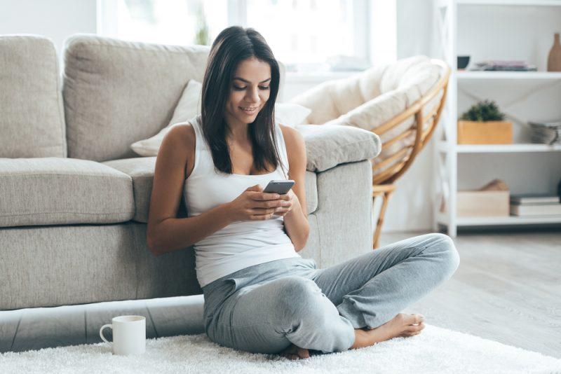 Eine Frau mit Kaffee sitzt auf dem Boden und einem Schlüssel auf ihrem Handy