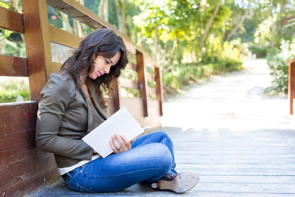 Auf der Brücke sitzt und schreibt etwas in ein Notizbuch ein junges trauriges Mädchen