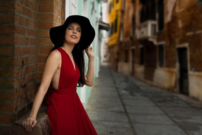 Auf der Straße steht eine Frau in einem roten Kleid mit einem Hut auf dem Kopf