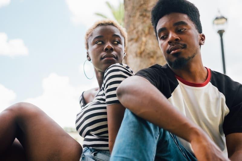Das junge Paar sitzt und sieht sich an