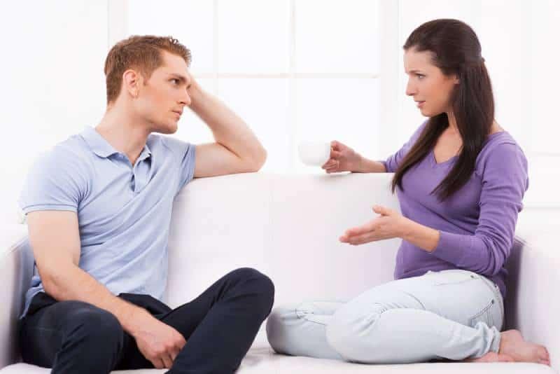 Deprimierter junger Mann, der auf der Couch sitzt und seine Freundin ansieht