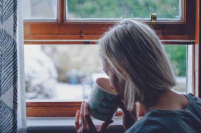 Die Blondine am Fenster trinkt Tee