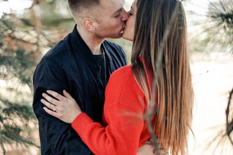 Ein Mädchen in einem roten T-Shirt wird von ihrem Freund geküsst