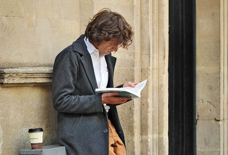 Draußen an der Wand gelehnt steht ein Mann und liest ein Buch