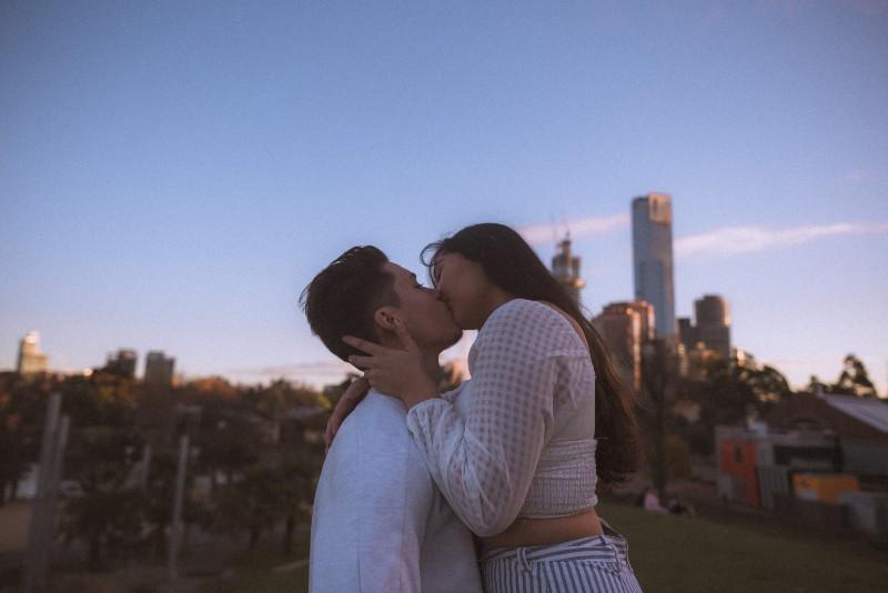 Ein Mädchen küsst einen Mann in der Stadt