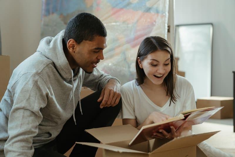 Ein Mädchen und ein Mann sitzen auf dem Boden und schauen sich ein Fotoalbum an
