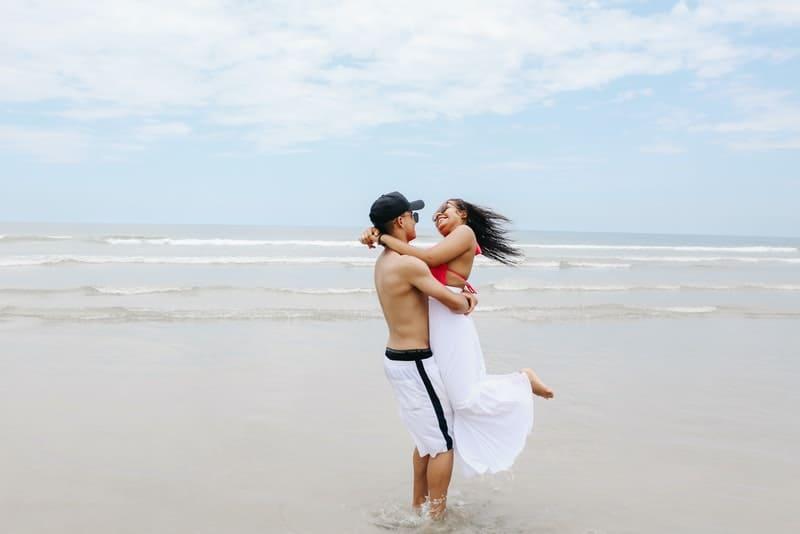 Ein Mann an einem Sandstrand hält ein lächelndes Mädchen in den Armen
