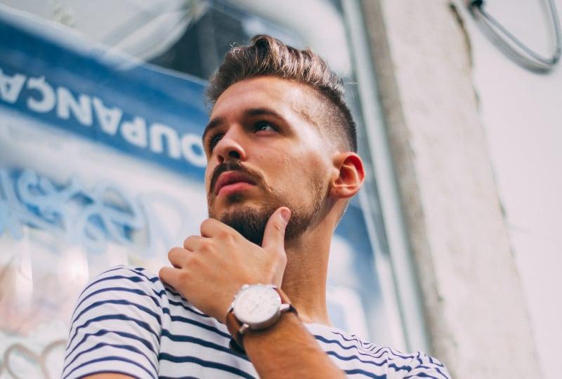 Ein Mann mit Bart und moderner Frisur posiert