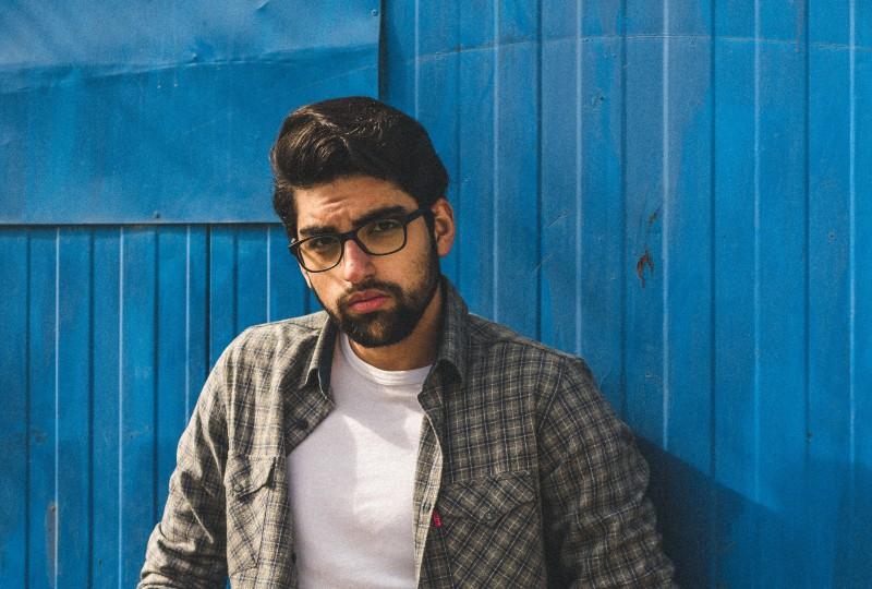Ein Mann mit Brille posiert an einer Wand