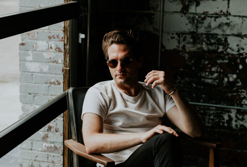 Ein Mann mit Brille sitzt auf einem Sessel