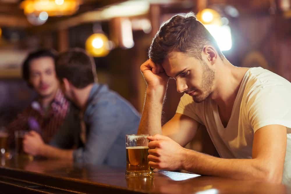 Ein Mann sitzt hinter einem Schlitten und trinkt
