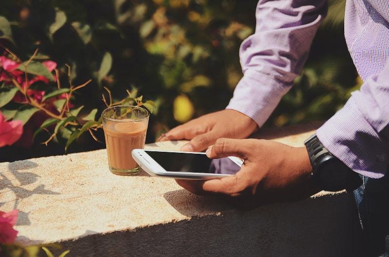 Ein Mann trinkt Kaffee und schreibt eine Nachricht auf sein Handy