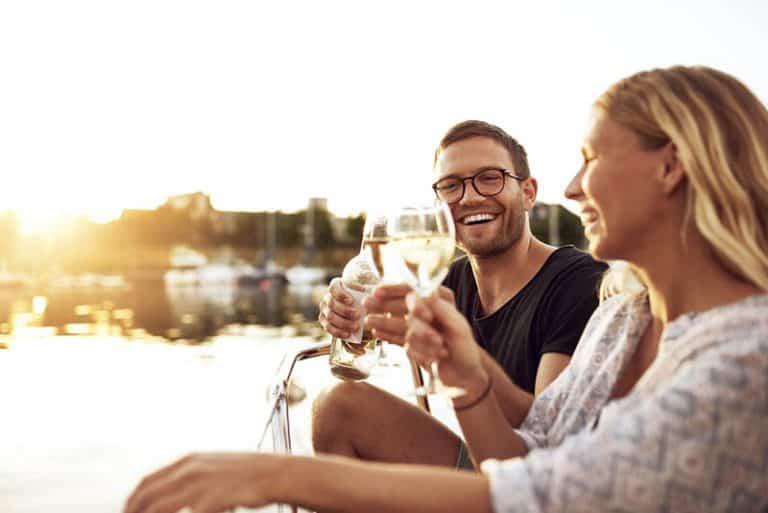 Ein Mann und eine Frau sitzen am Fluss und stoßen an