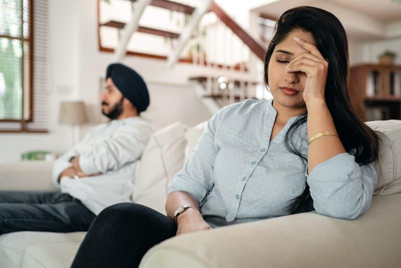 Ein Mann und eine Frau sitzen nach einem Streit auf der Couch