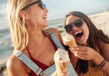 zwei lächelnde Freunde am Strand mit Eis in den Händen