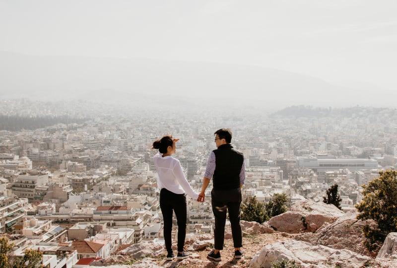 Ein Paar beobachtet die Stadt von der Spitze des Hügels aus
