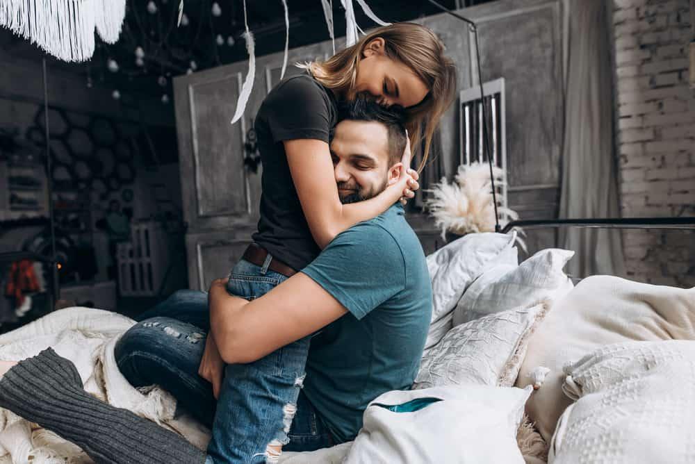Ein glückliches Liebespaar sitzt umarmt auf dem Bett