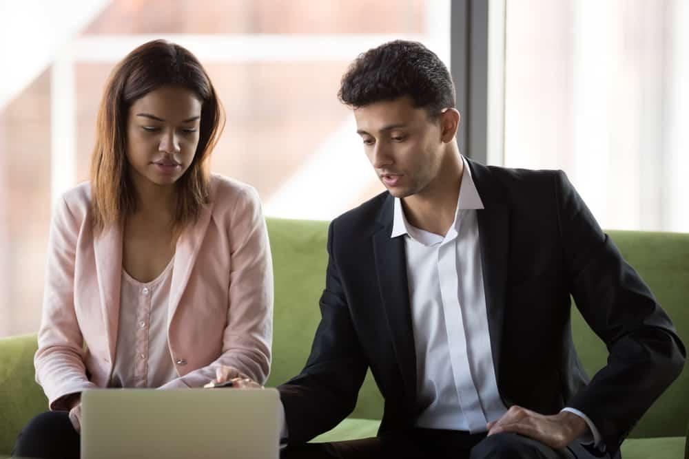 Ein gut gekleideter Mann erklärt einer Frau auf einem Laptop etwas