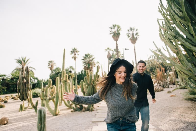 Ein lächelndes Mädchen und ihr Freund rennen Händchen haltend durch ein Kaktusfeld