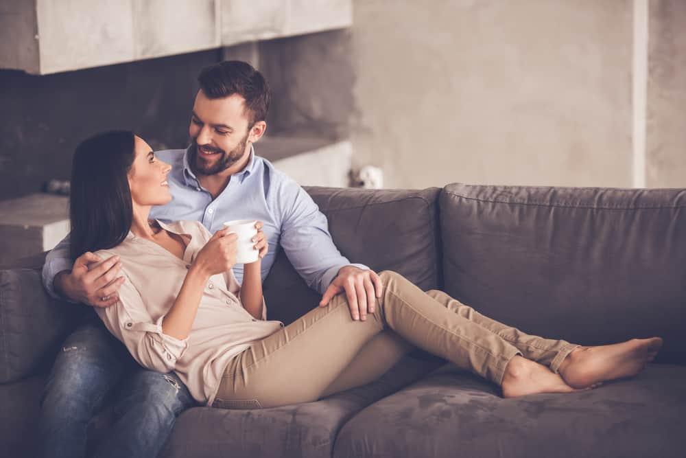 Ein lächelnder Mann und eine lächelnde Frau sitzen in einer Umarmung auf der Couch und unterhalten sich