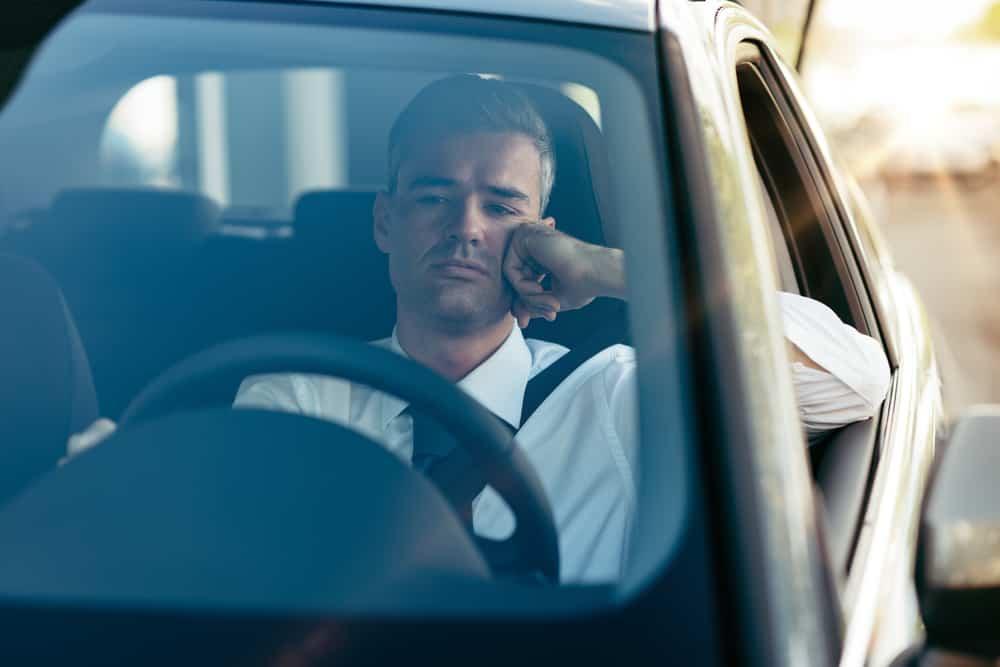 Ein trauriger Mann sitzt im Auto