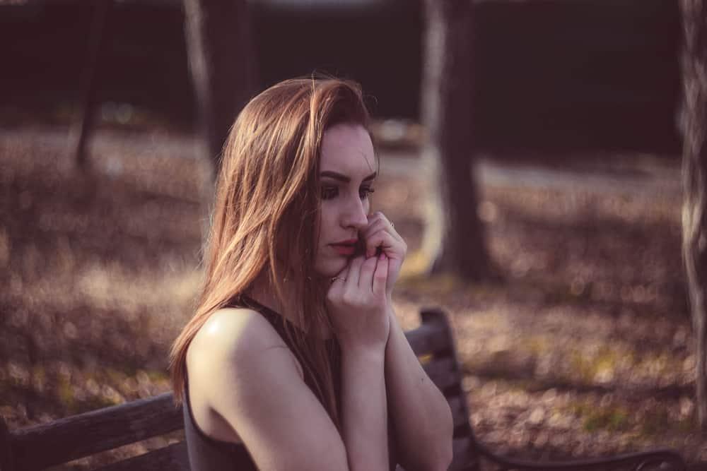 Ein trauriges rothaariges Mädchen sitzt im Herbst auf einer Parkbank