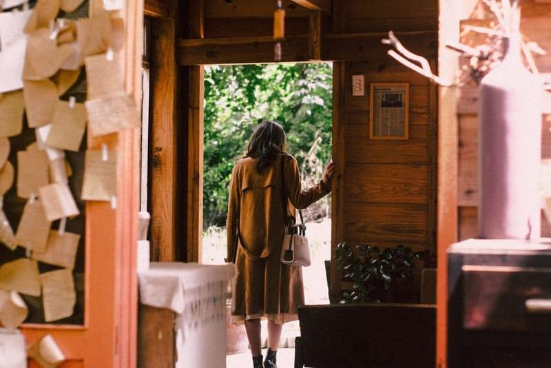Eine Frau in einem Mantel kommt aus dem Haus