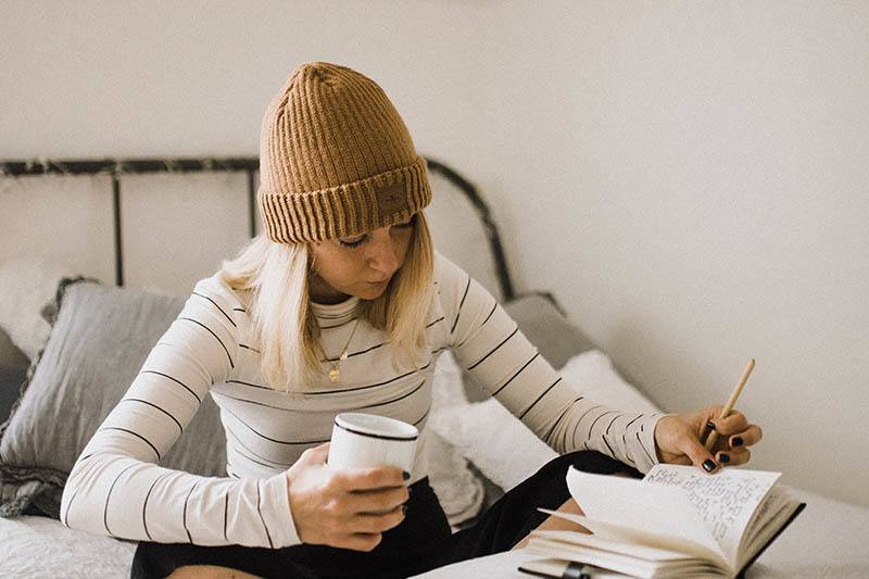 Eine Frau mit einer braunen Mütze sitzt und liest eine handschriftliche Handschrift